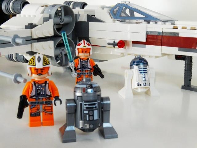 Minifiguren vor dem LEGO X-Wing 75218.