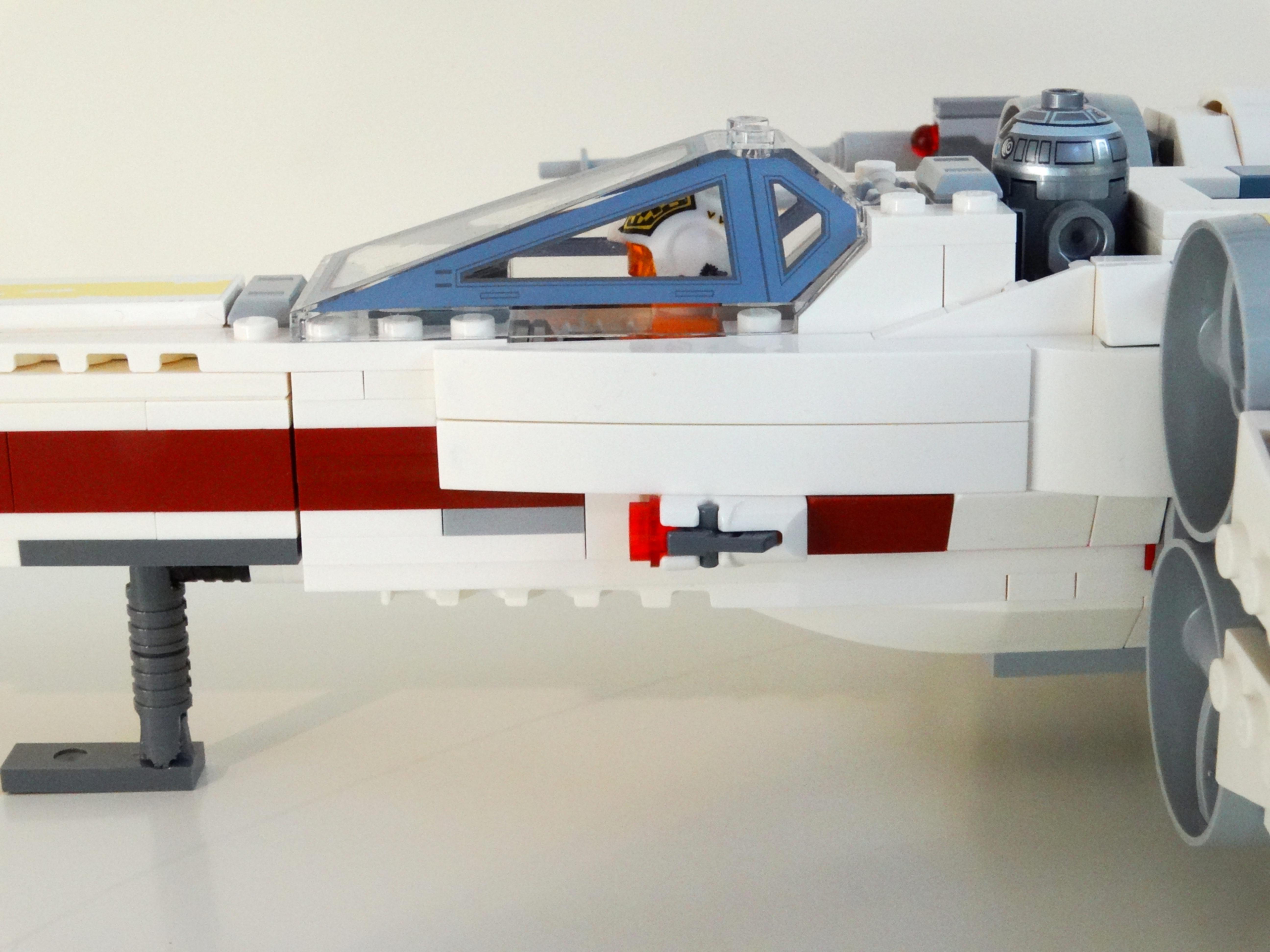 Seitenansicht des LEGO X-Wing 75218 mit Biggs Darklighter im Cockpit bei geschlossener Haube.