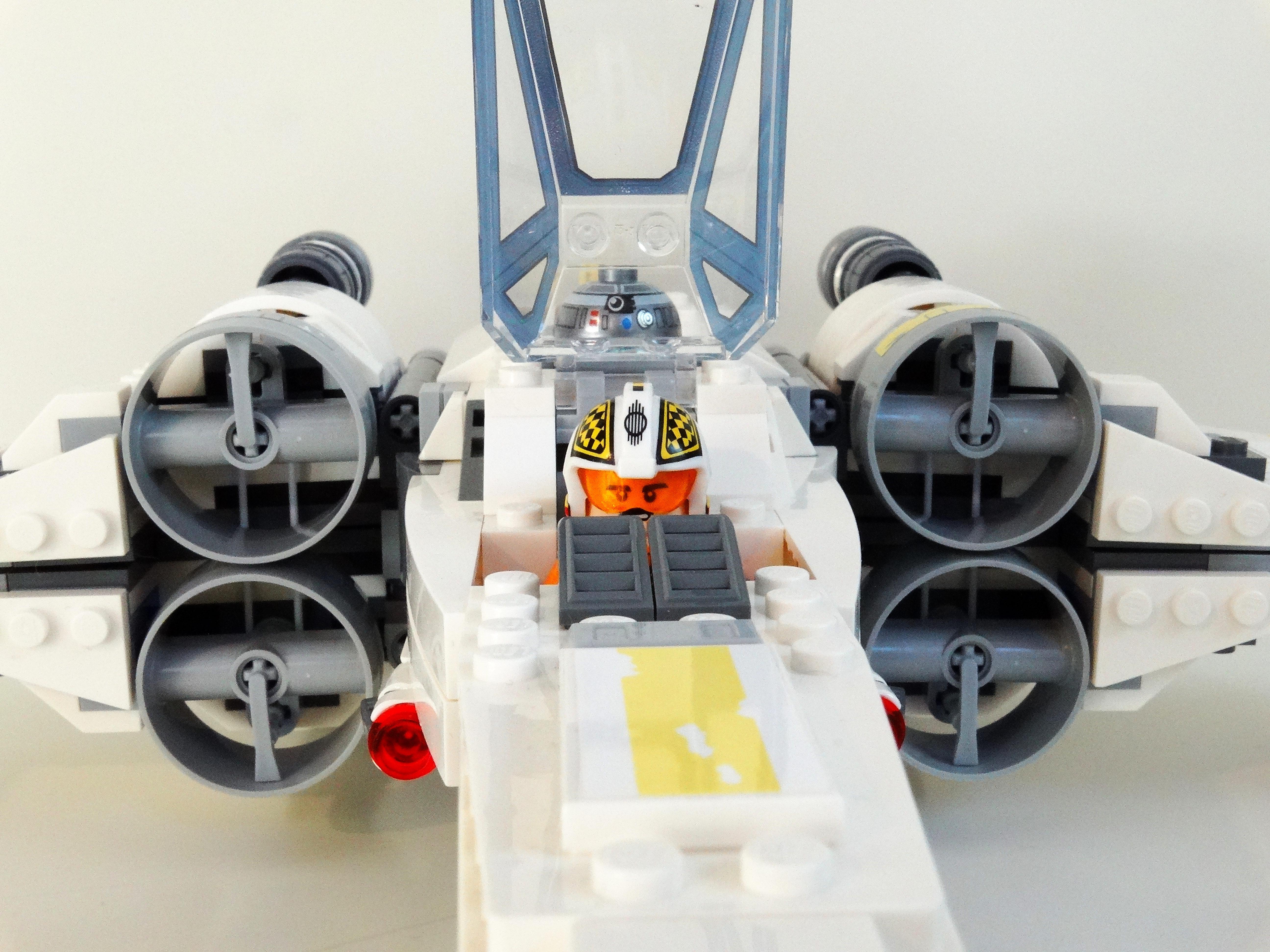 Nahaufnahme des Cockpits des Lego X-Wing 75218 mit Biggs Darklighter am Steuer bei geöffneter Haube.
