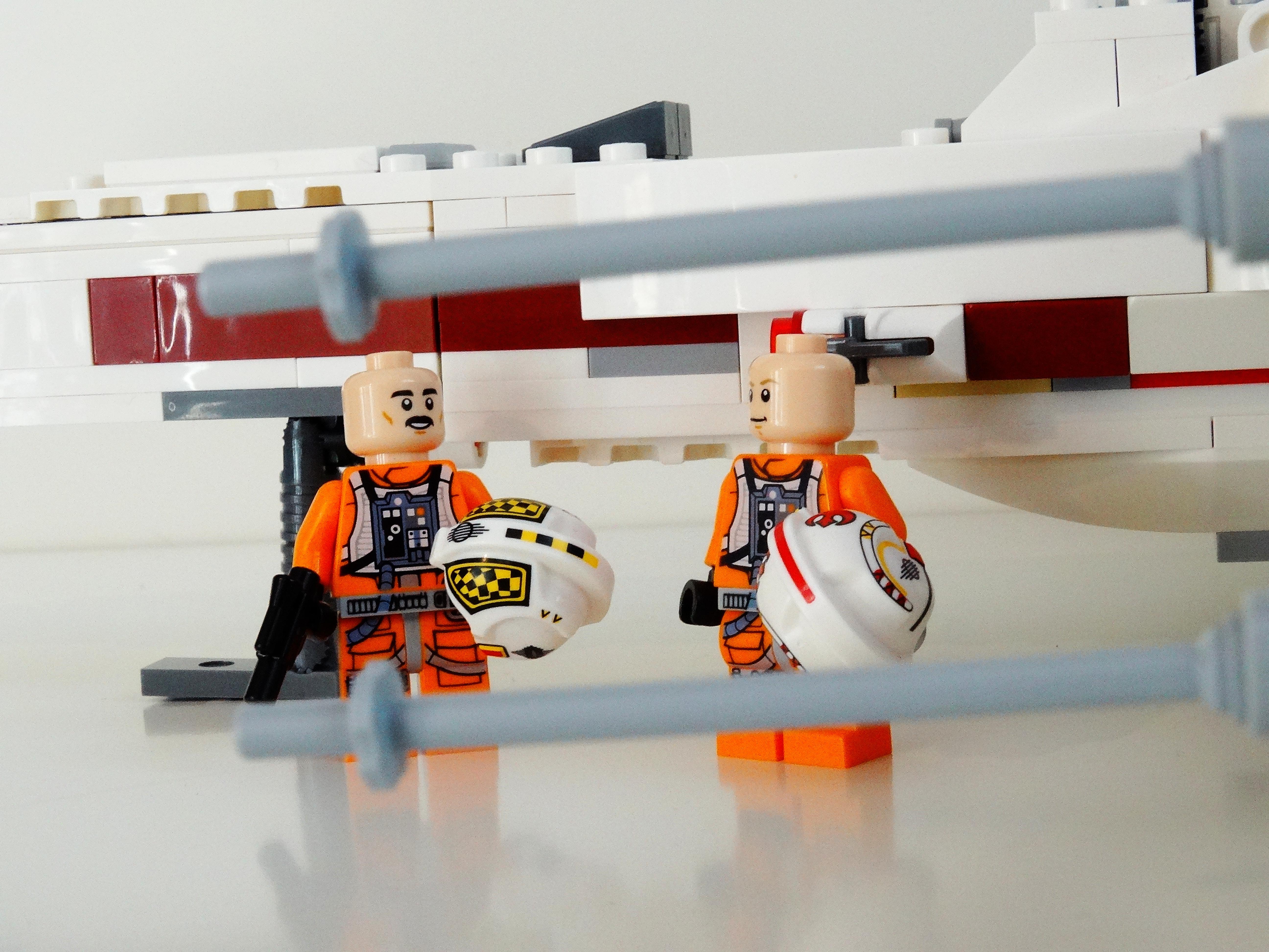 Nahaufnahme von Biggs Darklighter und Luke Skywalker mit abgezogenen Helmen am Lego X-Wing 75218.