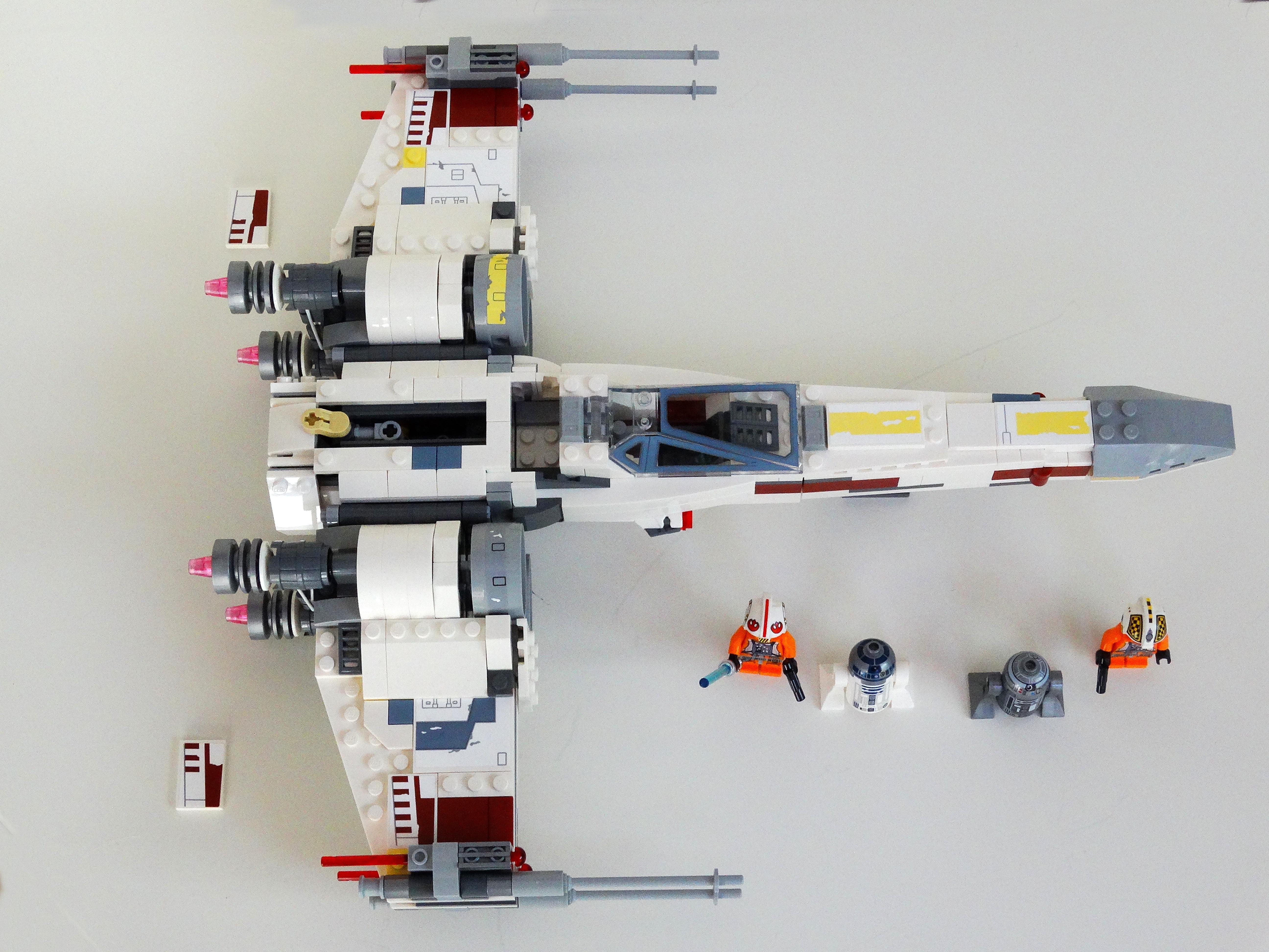 LEGO X-Wing 75218 aus der Vogelperspektive mitsamt Minifiguren und autauschbaren Kennungsplatten.