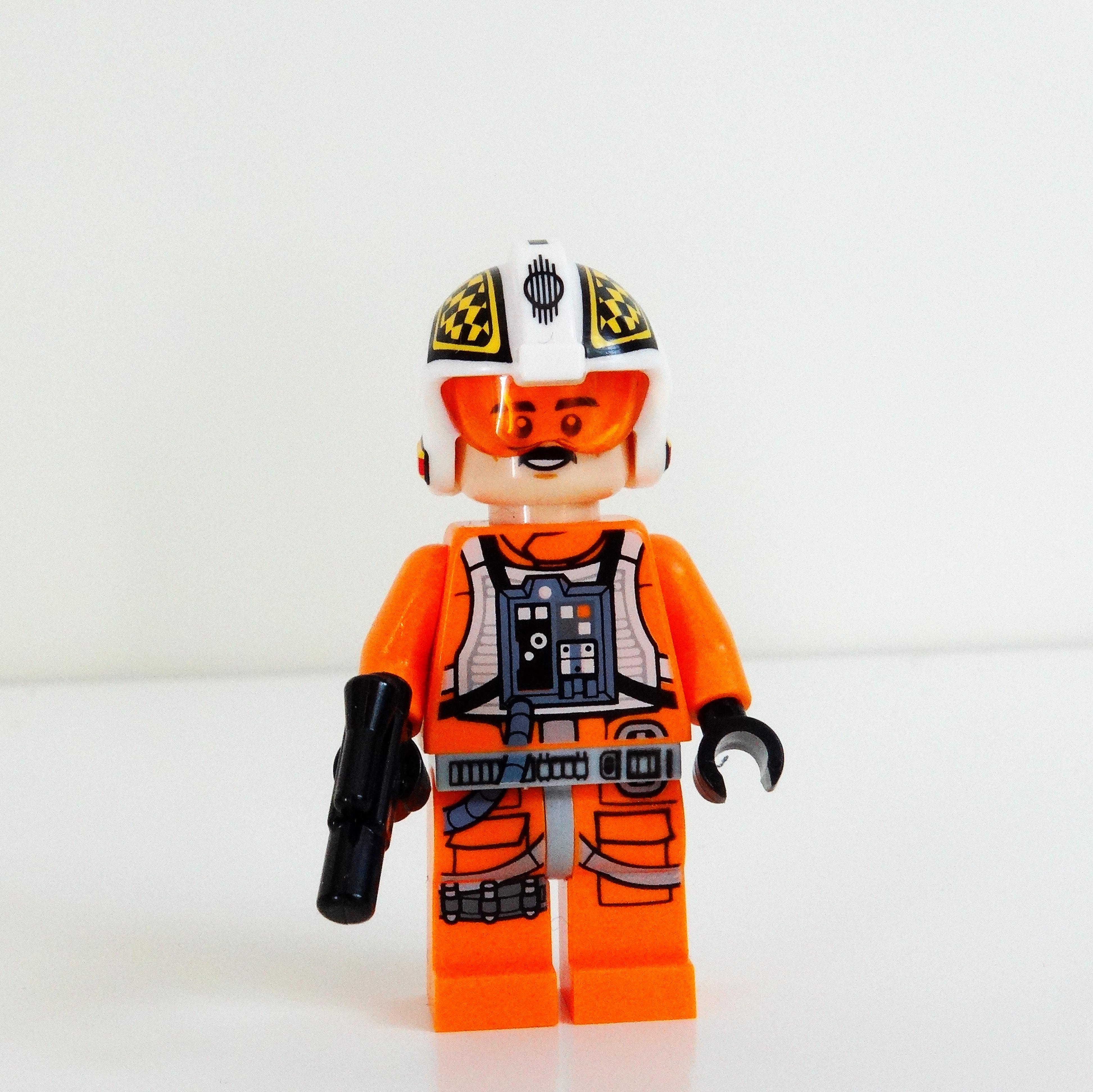 Vorderansicht von Biggs Darklighter mit aufgezogenem Helm und Blaster.