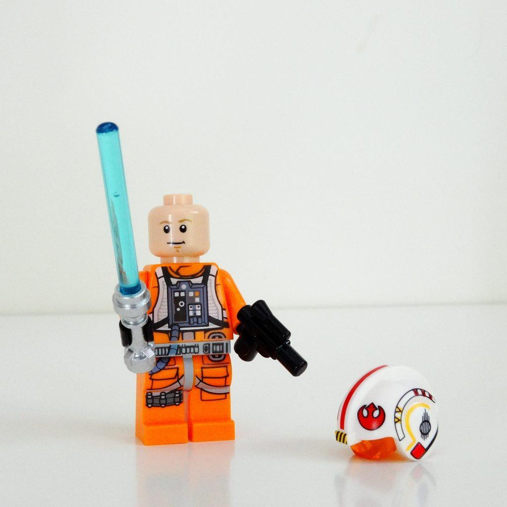 Vorderansicht von Luke Skywalker mit Lichtschwert und Blaster.