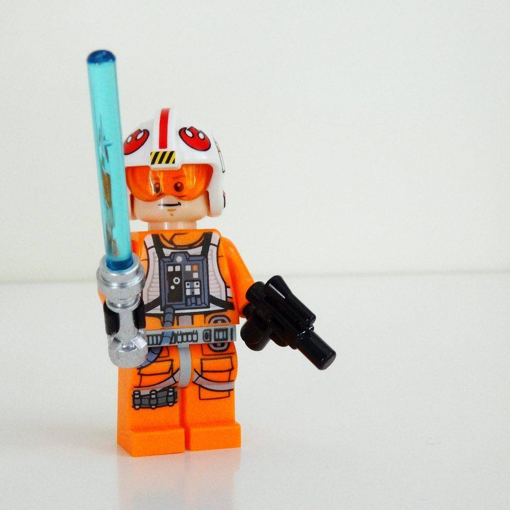 Vorderansicht von Luke Skywalker mit Lichtschwert, Blaster und aufgezogenem Helm.