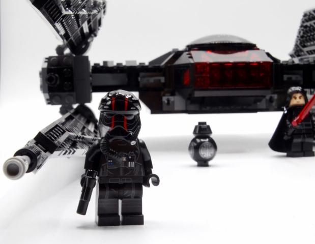 Tie-Pilot-Minifigur mit Blasterpistole vor dem Tie silencer, im Hintergrund stehen BB-9E und Kylo Ren mit rotem Lichtschwert.